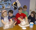 Five children in classroom with two having hands inside a blubber glove in small basins of water.