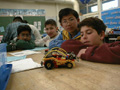 Students looking at a robotic car they built.